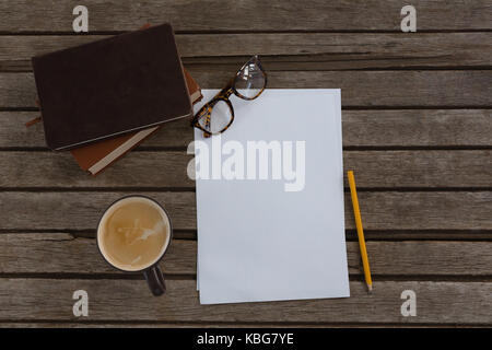 Overhead of organizer, coffee, spectacles, pencil and paper on wooden plank - Stock Photo