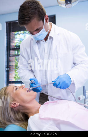 Dentist cleaning woman teeth while standing against wall at dental clinic - Stock Photo