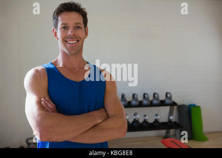 Portrait of confident male athlete with arms crossed standing in gym - Stock Photo