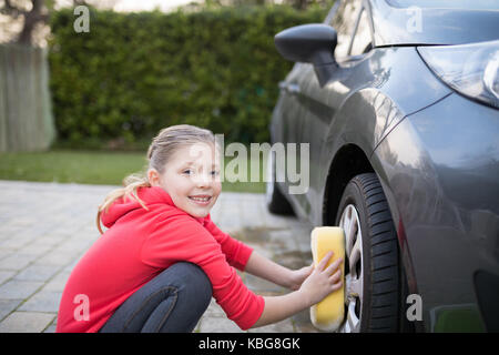 Portrait of teenage girl washing a car on a sunny day - Stock Photo