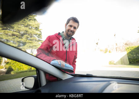 Portrait of man washing a car on a sunny day - Stock Photo