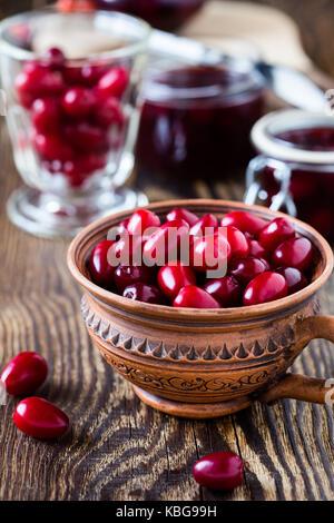 Ripe cornel berries in ceramic mug and dogwood jam on rural wooden background - Stock Photo