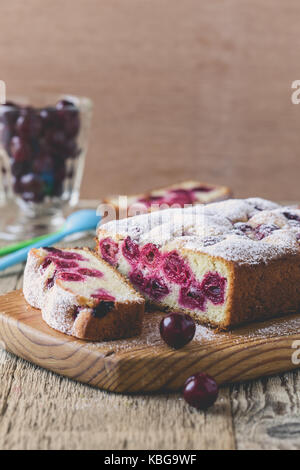 Homemade cherry cake on rustic wooden table - Stock Photo