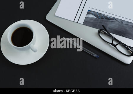 Overhead of black coffee, spectacles, pen, laptop and newspaper on black background - Stock Photo