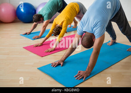 Male instructor guiding students in practicing downward facing dog pose at yoga studio - Stock Photo