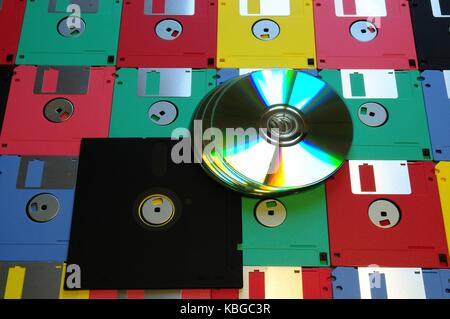 Old diskette 5 25 inches with 3.5 floppy disks of various colors with modern DVD. Background - Stock Photo