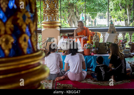 Monk reading the letter given by believers, who hope to be blessed, in Wat Suan Dok, Chiang Mai, Thailand - Stock Photo