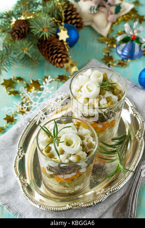 Homemade holiday snack Christmas table. Salad with marinated cucumber, potatoes, crab sticks, green peas and egg. - Stock Photo