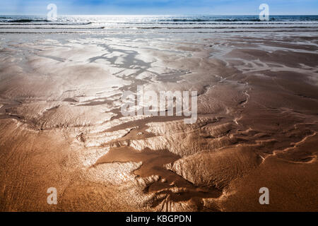 Glistening sand rivulets form abstract patterns on the beach. - Stock Photo