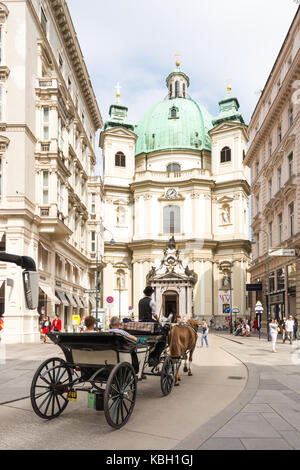 VIENNA, AUSTRIA - AUGUST 28: Tourists in a horse-drawn carriage called Fiaker at Peterskirche church in Vienna, - Stock Photo