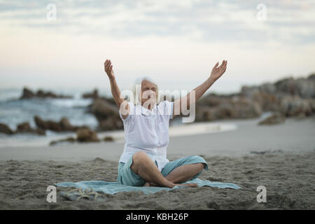 Senior woman with her hands raised sitting on the beach