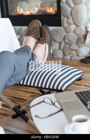 Professional with legs up on ottoman wearing slippers using computer next to cozy fireplace. - Stock Photo