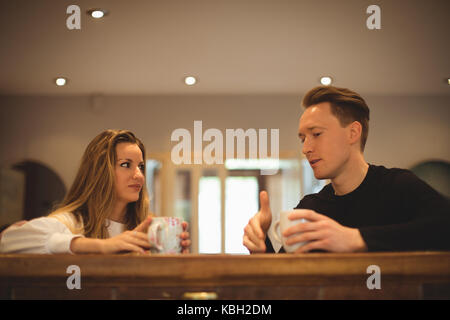 Couple interacting with each other while having coffee at home - Stock Photo