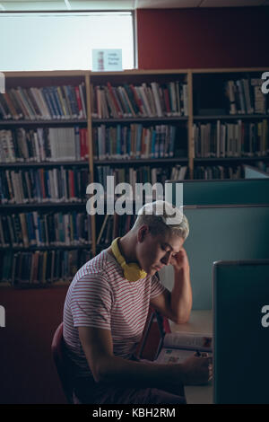 Attentive man studying at desk in library - Stock Photo