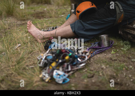 Low section of man relaxing on grass - Stock Photo