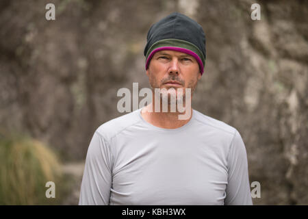 Confident man standing in front of mountain - Stock Photo