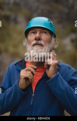 Close-up of senior man wearing protective helmet - Stock Photo