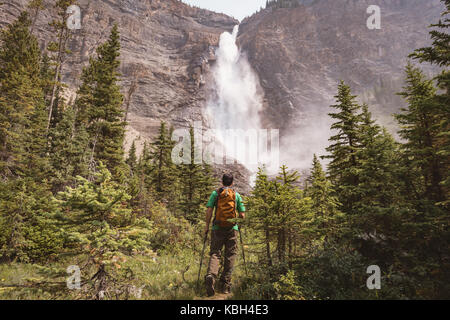 Man standing near waterfall in countryside - Stock Photo