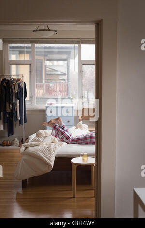 Low section of woman relaxing on bed at home - Stock Photo