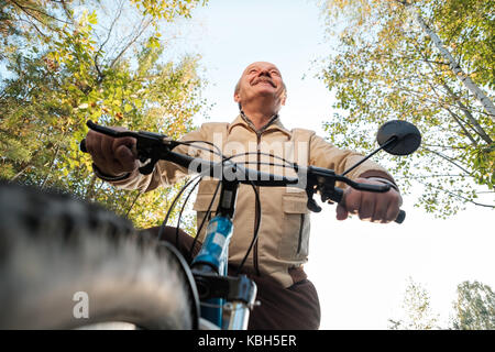 Senior man on cycle ride in countryside - Stock Photo