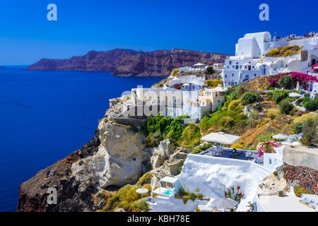 Oia town, Santorini island, Greece. Traditional and famous white houses and churches  with blue domes over the Caldera, - Stock Photo