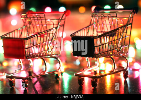 metal supermarket small cart on a background colored lights - Stock Photo