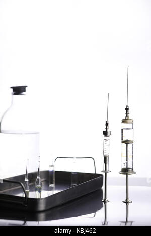 Old metal medical syringe and accessories on the table - Stock Photo