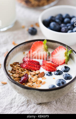 Yogurt with strawberries, blueberries and oats granola muesli in a bowl. Closeup view - Stock Photo