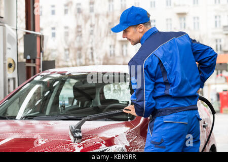 Mature manual worker washing red car at service station - Stock Photo