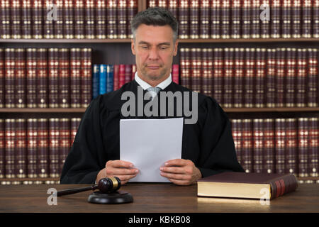 Mature male judge reading document at desk against bookshelf in courtroom - Stock Photo