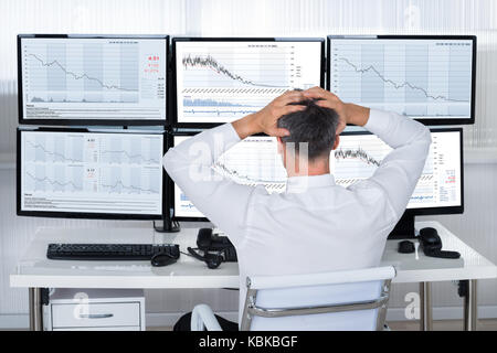 Rear view of stock trader with hands on head looking at graphs on screens - Stock Photo