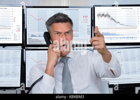 Angry male stock trader shouting while using telephone with computer screens in background - Stock Photo