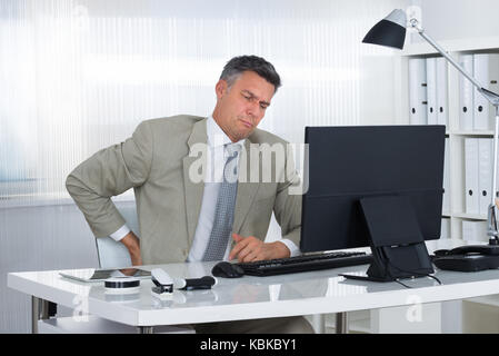 Mature businessman suffering from back pain at desk in office - Stock Photo
