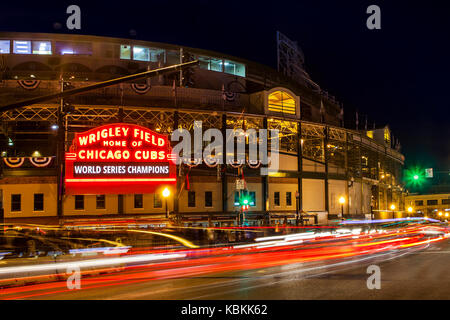 Traffic streaming past Chicago's Wrigley Field and entry sign announcing the Chicago Cubs as World Series Champions - Stock Photo