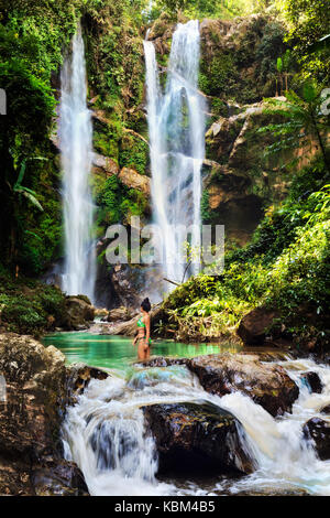 Happy excited woman tourist travel in nature rainforest and enjoy amazing waterfall hidden in tropical jungle - Stock Photo