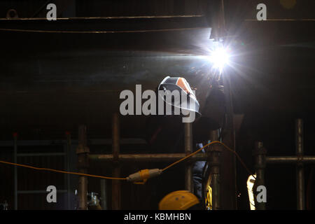 tradesman welding in shipyard - Stock Photo