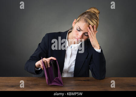 Sad young businesswoman holding empty purse at desk over gray background - Stock Photo