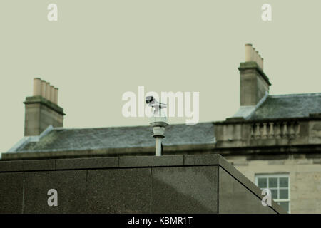 CCTV camera perched on top of a public building looking down, with Georgian terraces in the background - Stock Photo