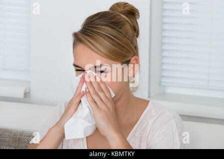 Young woman blowing nose while suffering from cold at home - Stock Photo