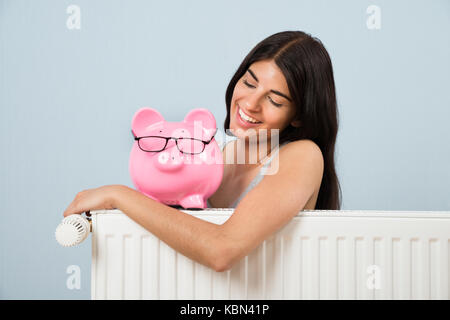 Young Woman Leaning On Radiator With Pink Piggybank At Home - Stock Photo