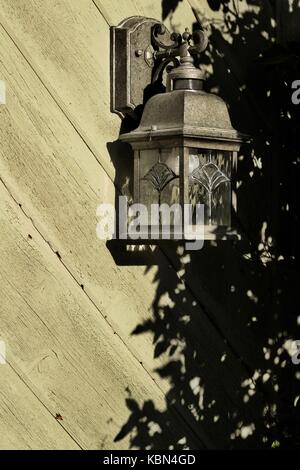Cedar sided wall and lantern with tree filtered sunlight casting late afternoon shadows onto its surface - Stock Photo