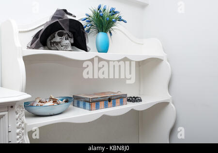Human skull in a white cabinet. Halloween theme - Stock Photo