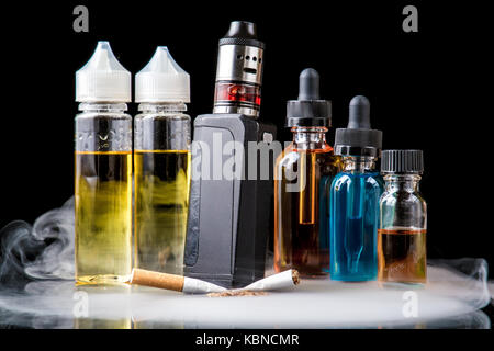 Modern vaporiser versus old tobacco cigarette in smoke - Stock Photo
