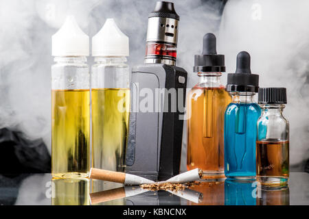 Modern vaporiser versus old tobacco cigarette in smoke cloud - Stock Photo