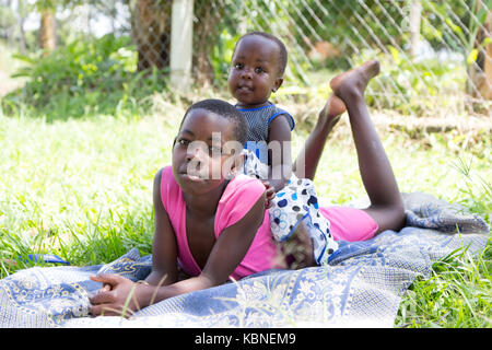 Makindu, Uganda. 27 April 2017. Two black girls lying in the grass. The little one is sitting on the older girls's - Stock Photo