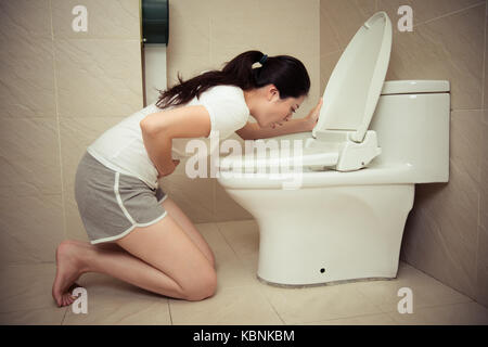 young beauty woman drunk feeling stomach uncomfortable and kneeling in front of bathroom toilet vomiting after party - Stock Photo