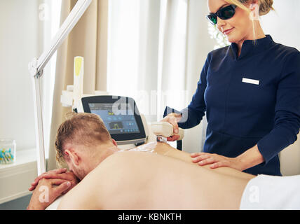 Young female beautician wearing protective glasses performing electrolysis on a man lying on a table in a beauty - Stock Photo