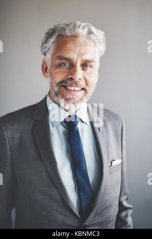 Portrait of a handsome mature businessman wearing a suit smiling confidently while standing alone in an office - Stock Photo