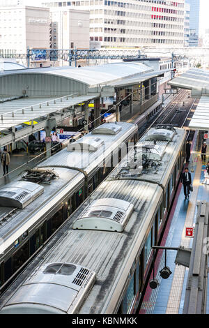 Japan, Osaka, Umeda. Osaka station city, overhead view of two trains at platforms - Stock Photo