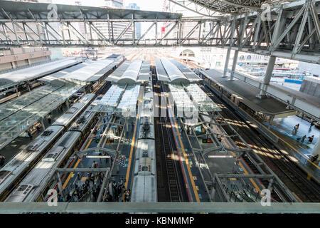 Japan, Osaka, Umeda. Osaka station city, overhead view of platforms with several trains. Daytime. - Stock Photo